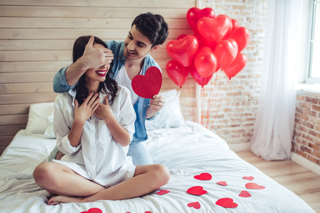 Foto de Beautiful young couple in bedroom. Celebrating Saint Valentine's Day. - Imagen libre de derechos