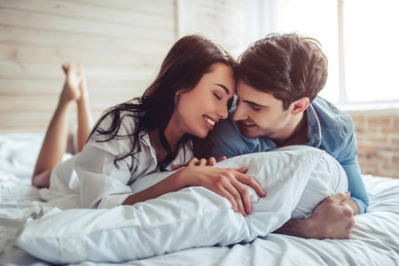 Foto per Beautiful young couple in bedroom is lying on bed. Enjoying spending time together. - Immagine Royalty Free