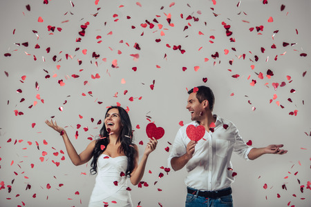 Beautiful romantic couple in love isolated on grey background with many little red flying hearts. Happy Saint Valentine\'s Day!