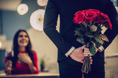 Photo for Beautiful loving couple is spending time together in modern restaurant. Attractive young woman in dress and handsome man in suit are having romantic dinner. Celebrating Saint Valentine's Day. - Royalty Free Image