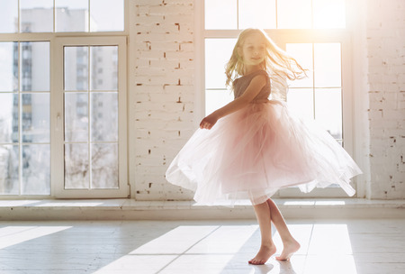 Photo for Cute little girl in beautiful dress is dancing at light sunny room - Royalty Free Image