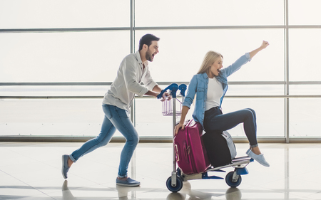 Photo pour Romantic couple in airport. Attractive young woman and handsome man with suitcases are ready for traveling. Having fun on luggage trolley while waiting for departure. - image libre de droit