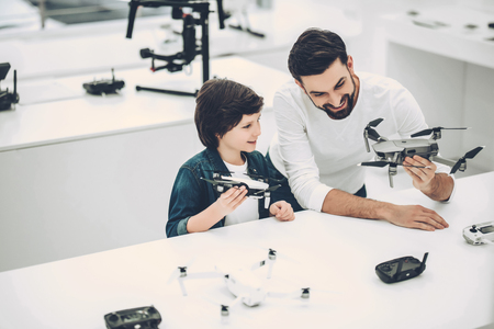 Handsome young man and his cute son are in modern light quadcopter store. Choosing the appropriate drone