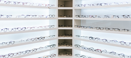 Photo pour Big choice of eyeglasses on shelves in ophthalmology clinic. Modern light ophthalmology clinic. - image libre de droit
