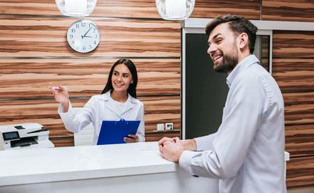 Foto de Young female doctor  and handsome patient are standing on reseption desk in modern clinic - Imagen libre de derechos