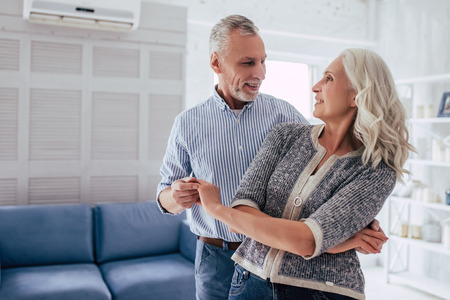 Photo for Love lives forever! Senior couple at home. Handsome old man and attractive old woman are enjoying spending time together while dancing. - Royalty Free Image