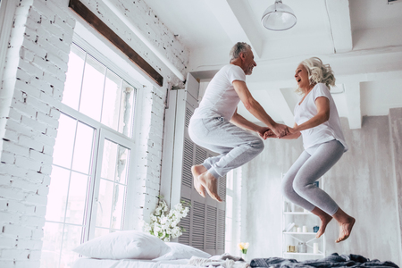 Foto de Love lives forever! Senior couple at home. Handsome old man and attractive old woman are enjoying spending time together. Having fun and jumping in bed. - Imagen libre de derechos
