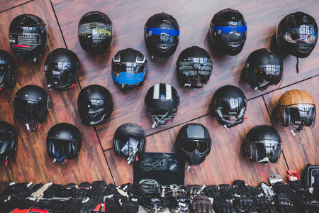 Photo for Motorcycles and accessories in modern motorcycle shop. Biker stuff. Helmets on wooden background. - Royalty Free Image
