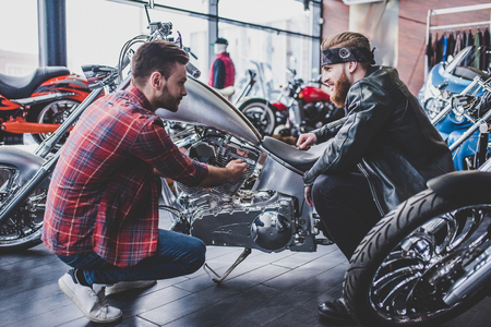 Photo pour Two men in motorcycle shop. Customer and salesman. Shop assistant is helping bearded man in choosing new vehicle, motorcycle accessories and other biker stuff. - image libre de droit