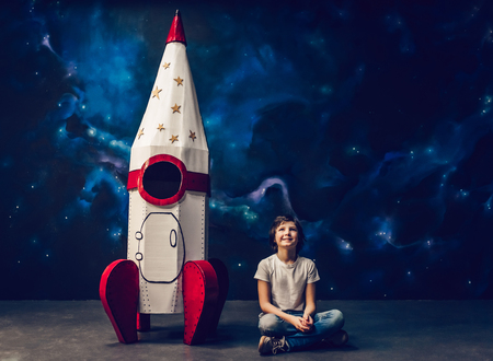 Boy is sitting near toy rocket on space background.
