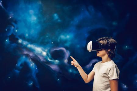 Photo pour Little boy wearing glasses of virtual reality on space background. - image libre de droit