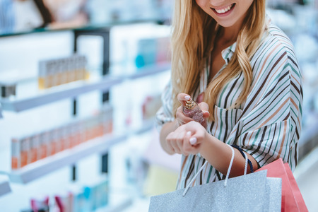 Photo for Cropped image of attractive young girl is doing shopping with shopping bags in perfume store in modern mall. - Royalty Free Image
