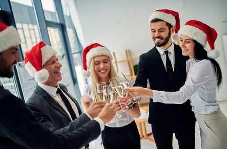 Foto de Merry Christmas and Happy New Year! Group of office workers celebrating winter holidays together at work. Business people drinking champagne in office. - Imagen libre de derechos
