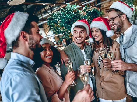 Photo for Merry Christmas and Happy New Year 2020!Multiracial young creative people are celebrating holiday in modern office. Group of young business people are drinking champagne in coworking. Successful hipster team of freelancers. - Royalty Free Image