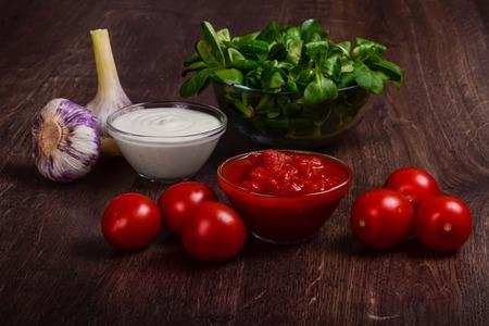 Foto de Homemade sauce on a dark wood table. Homemade tomato and garlic cream sauces. - Imagen libre de derechos