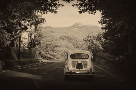 Photo pour Sepia photo of a retro car going to mountains - image libre de droit