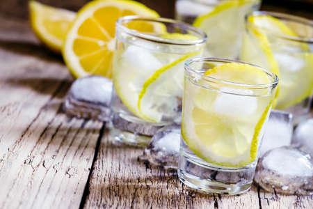 Photo pour Lemon vodka with ice, vintage wooden background, selective focus - image libre de droit