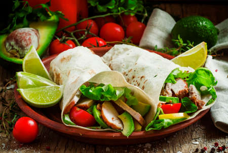 Foto für Fresh roll shawarma (doner) with meat, avocado, cherry tomatoes, peppers and lettuce on a clay plate, dark toned image, street food concept, selective focus - Lizenzfreies Bild