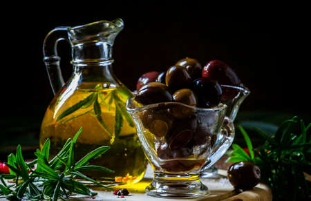 Photo for Greek olives in a glass bowl and oils, dark wood background, selective focus - Royalty Free Image