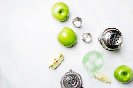 Photo for Alcoholic cocktail with green apple and dry vermouth, syrup, lemon juice and ice cubes. Bar tools, gray stone background, top view - Royalty Free Image
