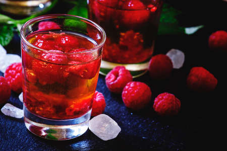 Photo pour Alcoholic cocktail with strong alcohol, syrup and fresh raspberries, black background, selective focus - image libre de droit