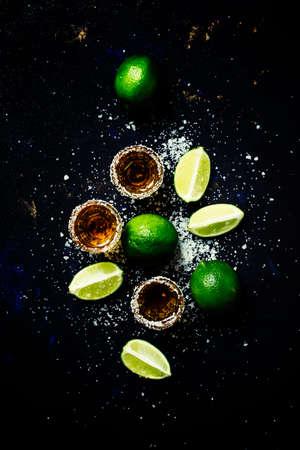 Photo pour Golden mexican tequila with lime and sea salt, black background, top view - image libre de droit