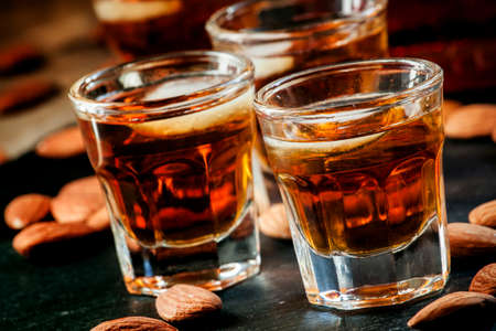 Photo pour Cold whiskey with ice in a glass and a snack almonds, selective focus - image libre de droit