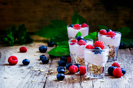 Photo for Sweet berry dessert with oatmeal, yogurt, blueberries and raspberries, vintage wooden background, selective focus - Royalty Free Image