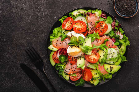 Photo for Keto diet salad with salted salmon in a black plate - Royalty Free Image