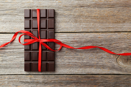 Photo for Dark chocolate bar with red bow on grey wooden background - Royalty Free Image