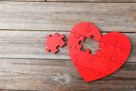 Photo pour Red puzzle heart on grey wooden background - image libre de droit
