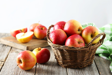 Red apples in basket on grey wooden background