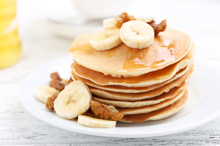 Tasty pancakes with banana and walnut on white wooden background