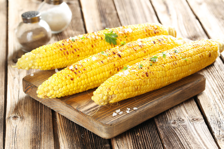 Foto für Fresh tasty grilled corn with butter on brown table and cutting board - Lizenzfreies Bild