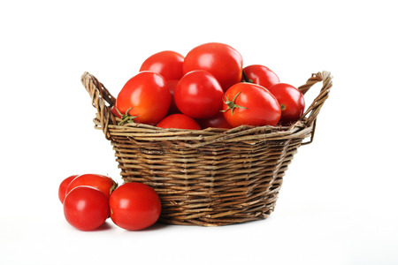 Fresh red tomatoes in basket isolated on whiteの写真素材