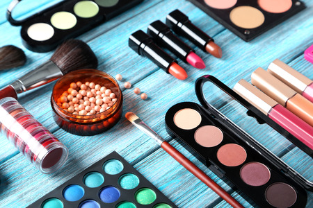 Photo for Makeup brush and cosmetics on blue wooden table - Royalty Free Image