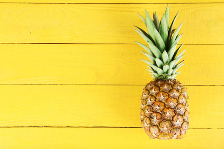 Photo pour Ripe pineapple on a yellow wooden background - image libre de droit