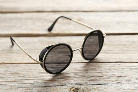 Photo pour Black sunglasses on a grey wooden table - image libre de droit