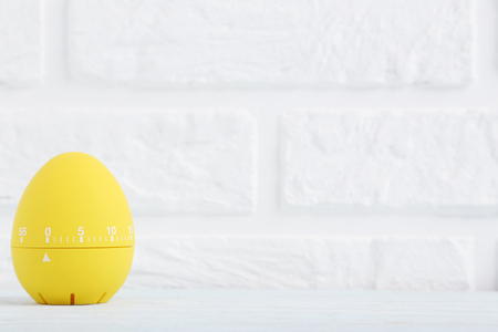 Photo pour Yellow egg timer on a brick wall background - image libre de droit