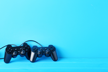 Black joysticks on a blue wooden table