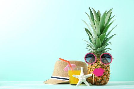Ripe pineapple with sunglasses and glass of juice on mint background