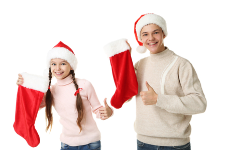 Photo pour Young girl and boy in santa hats holding christmas socks on white background - image libre de droit