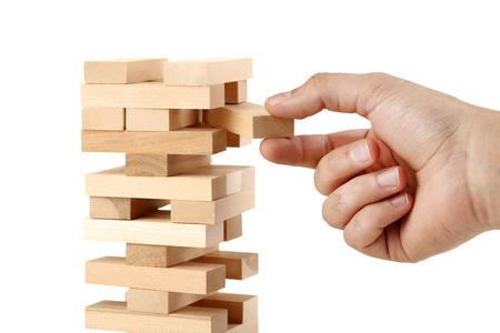 Foto de Male hand playing wooden blocks tower game on white background - Imagen libre de derechos