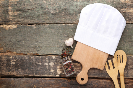 Photo pour Chef hat with cutting board, pepper and garlic on grey wooden table - image libre de droit