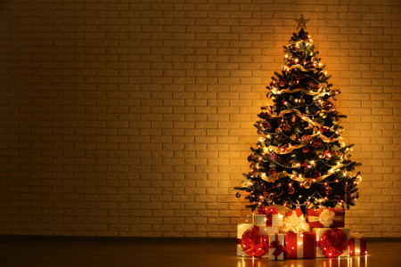 Foto de Christmas tree with decorations and gift boxes on brick wall background - Imagen libre de derechos