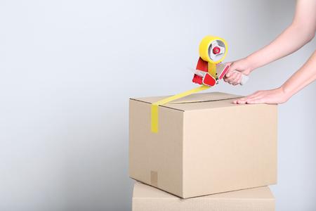 Foto de Female's hands packaging cardboard box with dispenser on grey background - Imagen libre de derechos