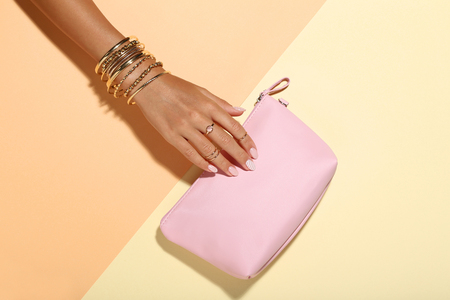Photo pour Female hand with bracelets and handbag on colorful background - image libre de droit