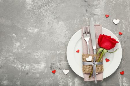 Foto de Kitchen cutlery with red rose in white plate on wooden table - Imagen libre de derechos