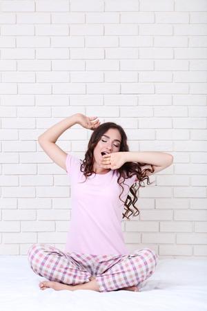 Photo for Yawning girl in pajamas sitting on white bed - Royalty Free Image