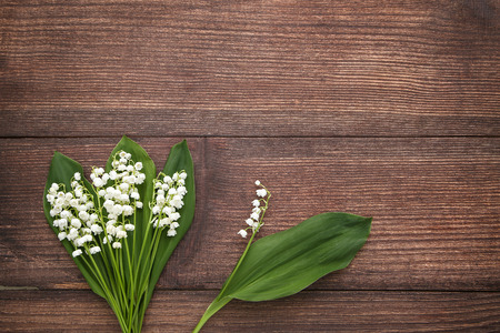 Photo pour Lily of the valley flowers on brown wooden table - image libre de droit